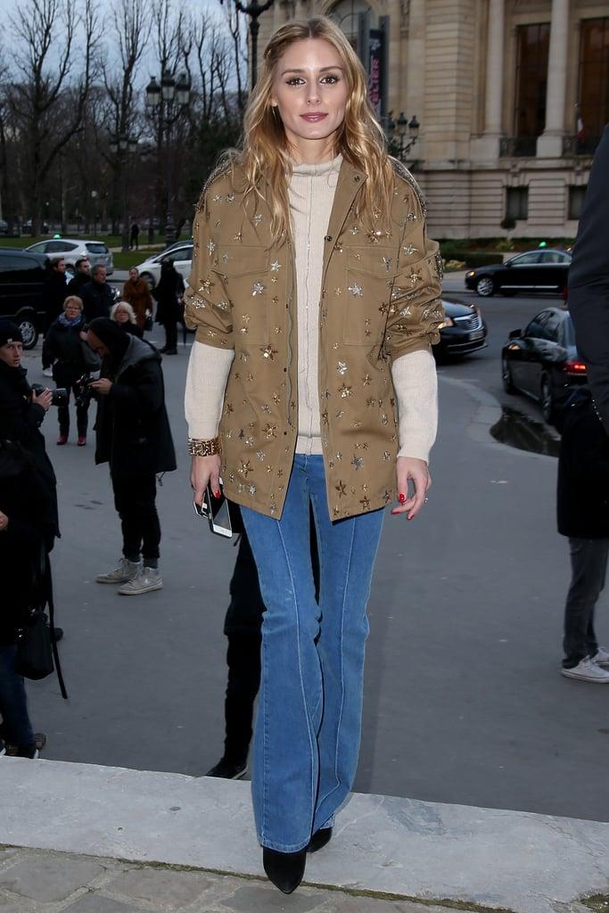 Оливия Палермо в синих джинсах клеш и коричневой куртке