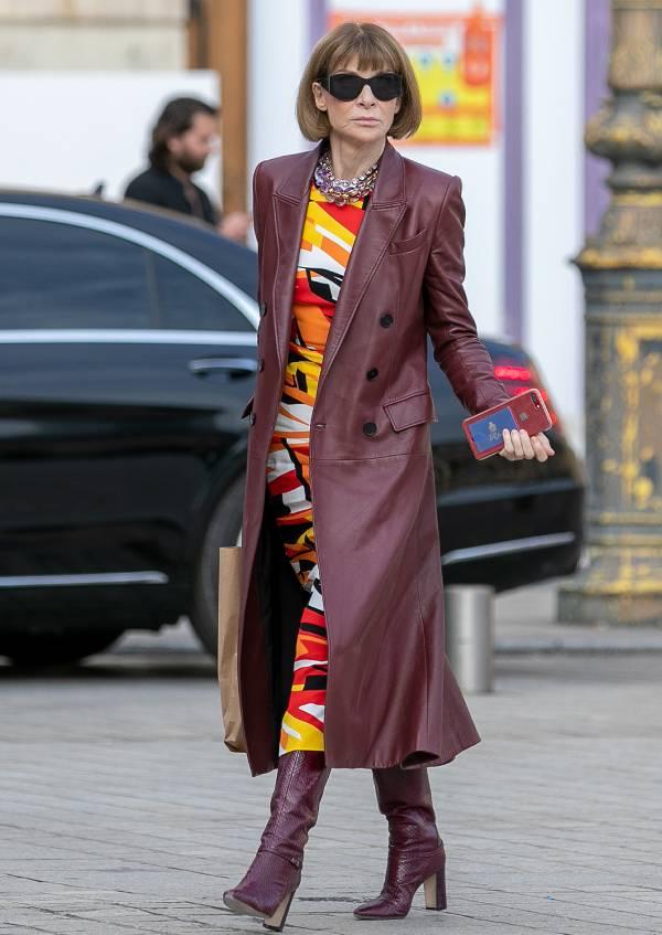Анна Винтур в бордовом кожаном плаще, яркое платье и высокие сапоги