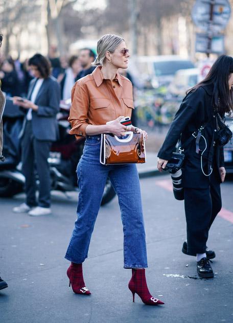 Девушка в укороченных джинсах, коричневая рубашка и красные ботильоны