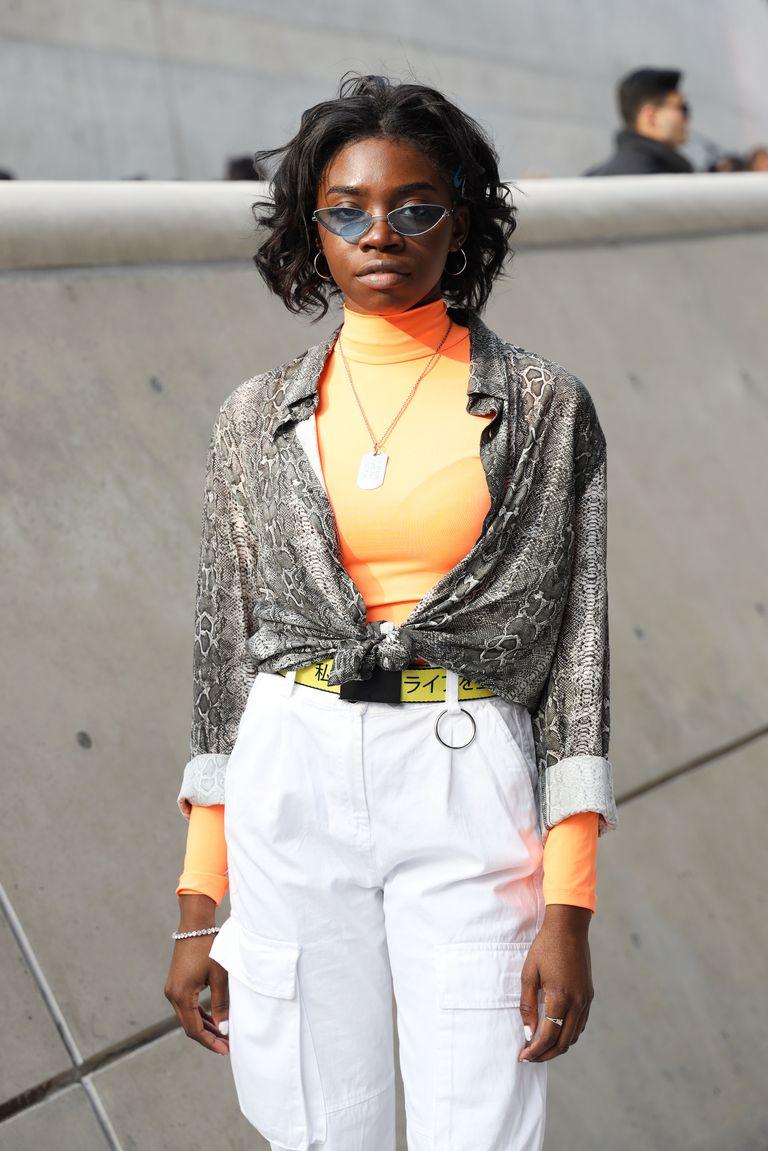 Девушка в белых брюках, оранжевой водолазке и рубашке со змеинным принтом