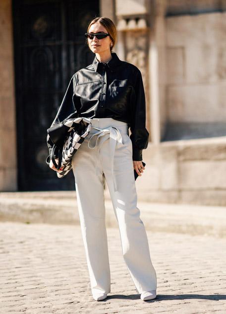 Девушка в белых широких брюках с поясом и черная кожаная сумка