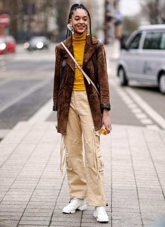 Девушка в бежевых брюках, желтая водолазка и коричневый жакет