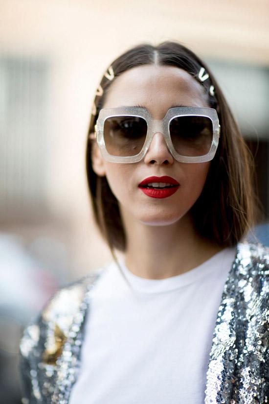 Девушка в блестящей куртке и больших очках с блестками