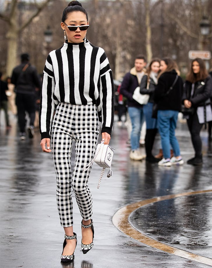 Девушка в черно белом свитере в полоску и брюках в клетку