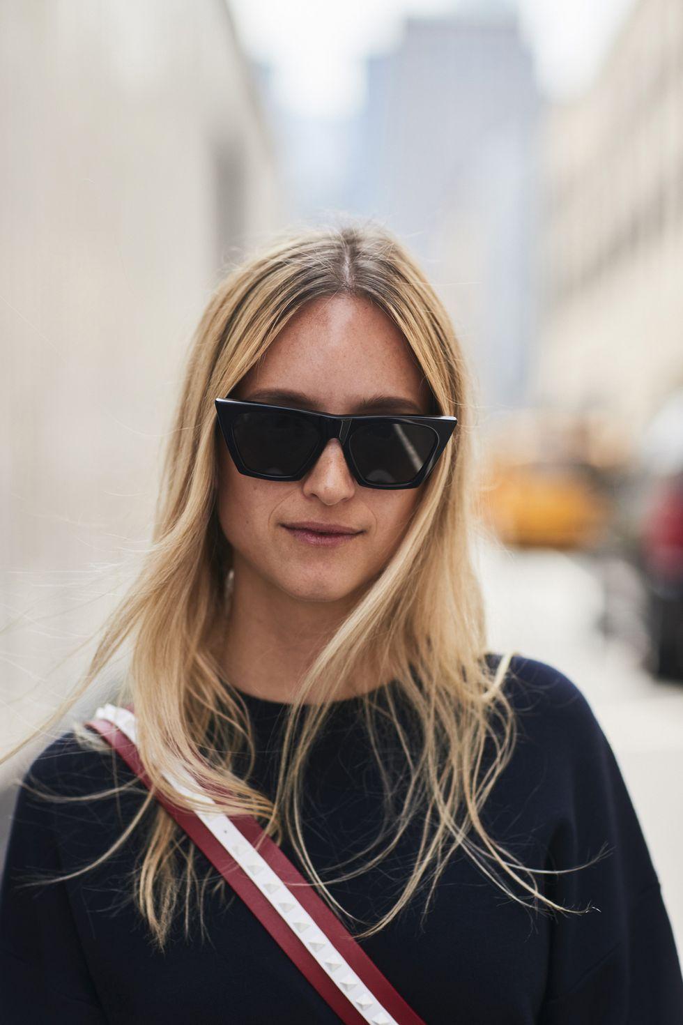 Девушка в черном джемпере и больших солнцезащитных очках