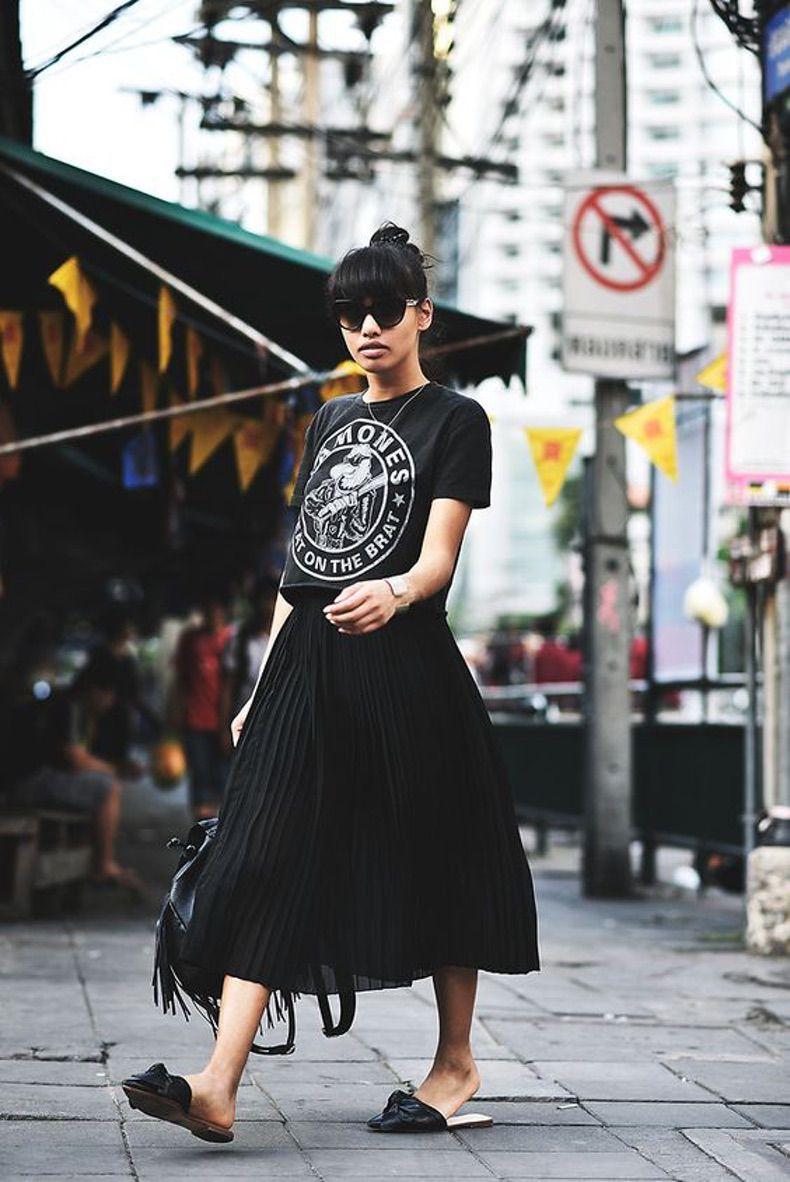 Девушка в черной плиссированной юбке и футболка с принтом
