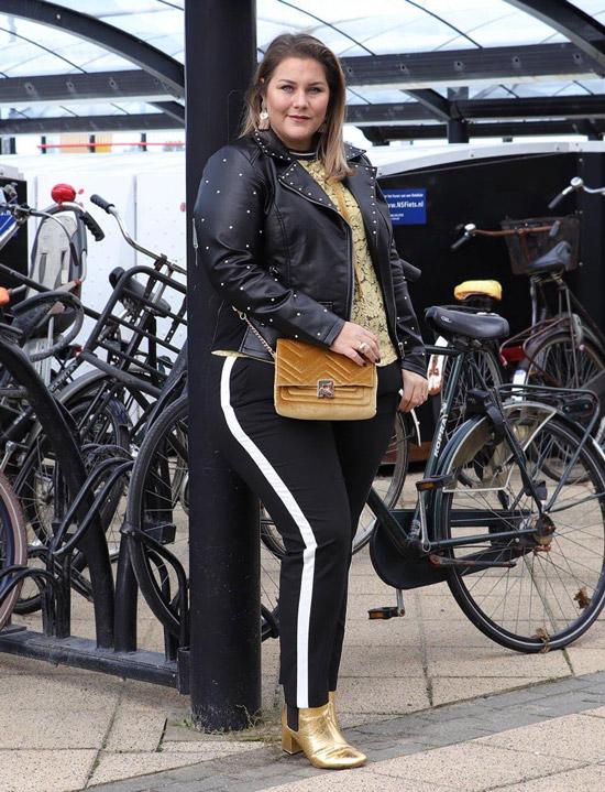 Девушка в черных брюках с ломпасами, куртка косуха и золоты ботильоны