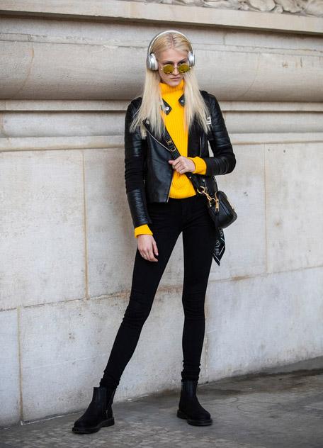 Девушка в черных леггинсах, косуха и оранжевый свитер