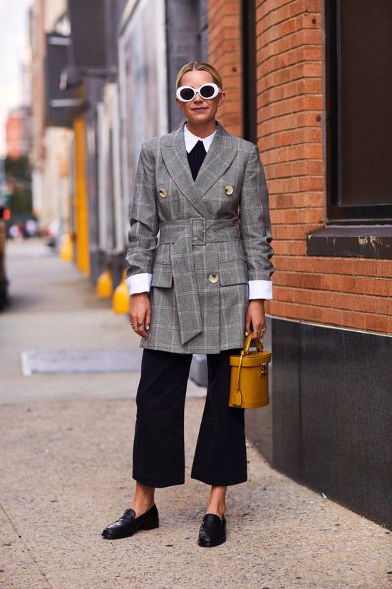Девушка в черных укороченных брюках, серый блейзер в клетку и желтая сумочка