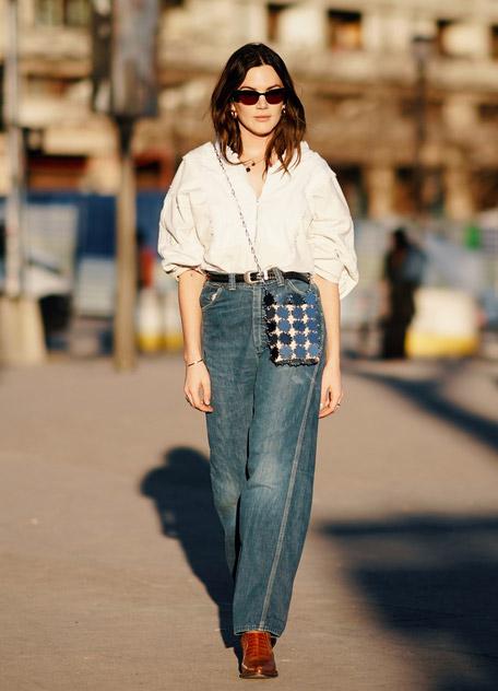 Девушка в белой блузке и широкие джинсы с ремнем