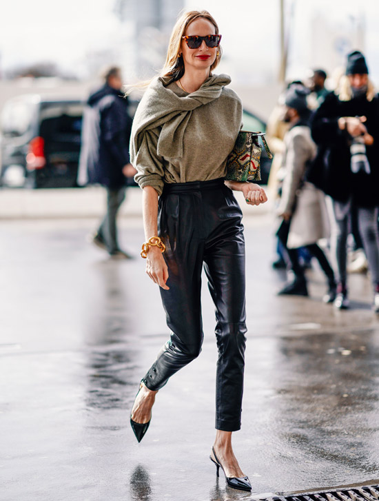 Девушка в кожаных брюках, черные туфли и джемпер
