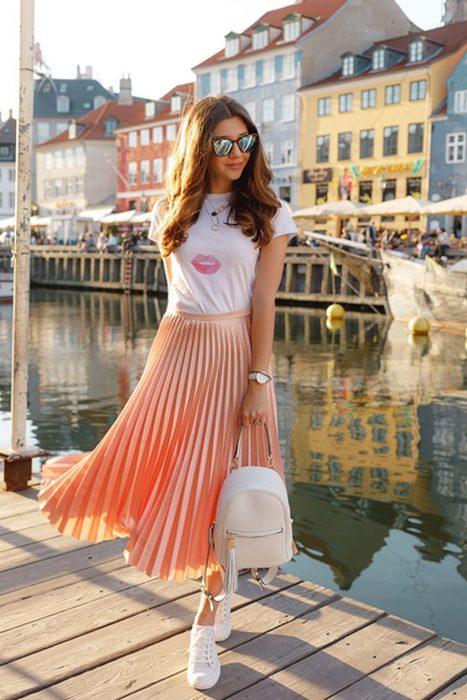 Девушка в персиковой плиссированной юбке и белой футболке, кеды