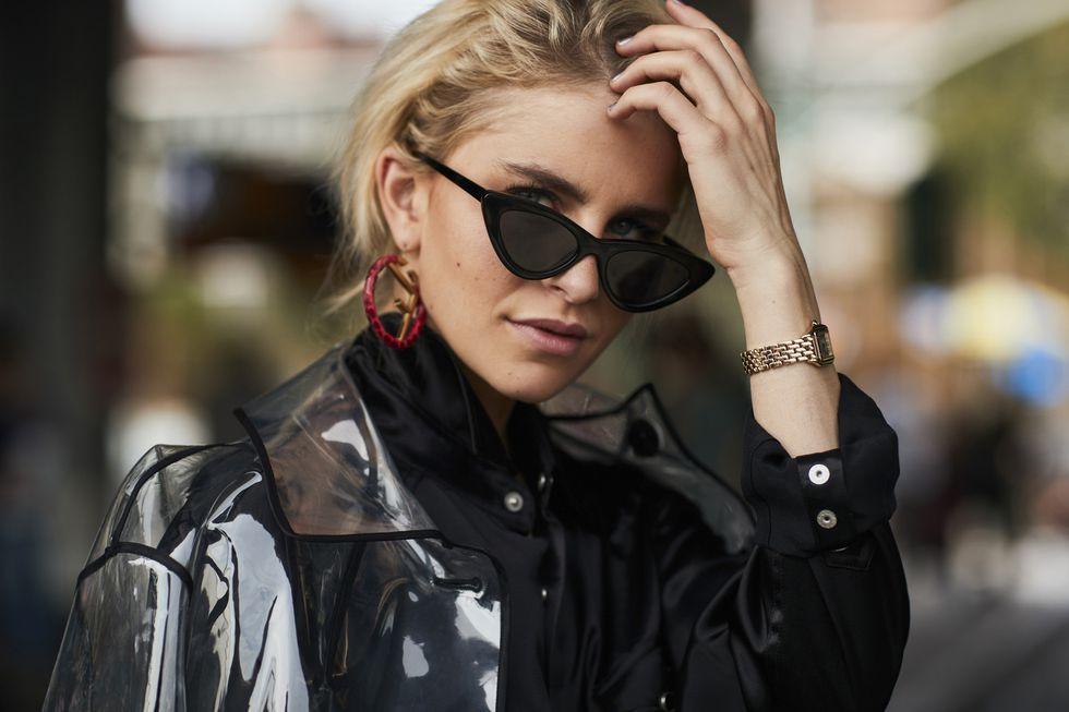 Девушка в прозрачном плаще и солнцезащитных очках