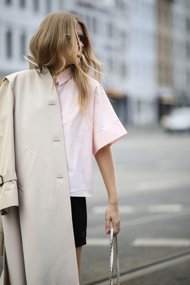 Девушка в розовой рубашке с короткими укавами и бежевом плаще