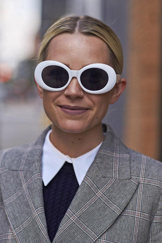 Девушка в сером блейзере в клетку и солнцезащитных очках с белой оправой