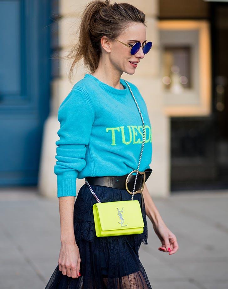 Девушка в синем джемпере, синей юбке и желтая сумка