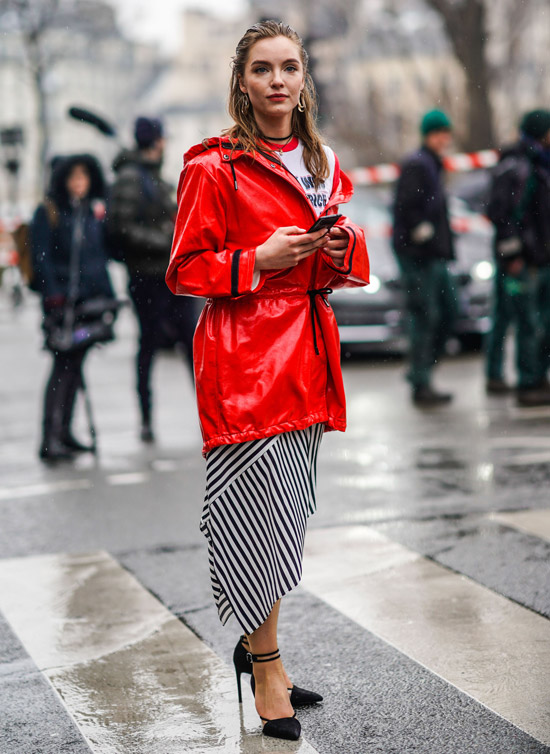 Девушка в юбке в полоску, красная лакированная куртка и черные туфли