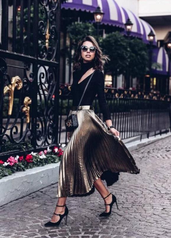 Девушка в золотой плиссированной юбке и черная водолазка