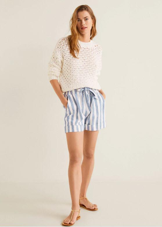 Модель в белом свитере и шортах в полоску