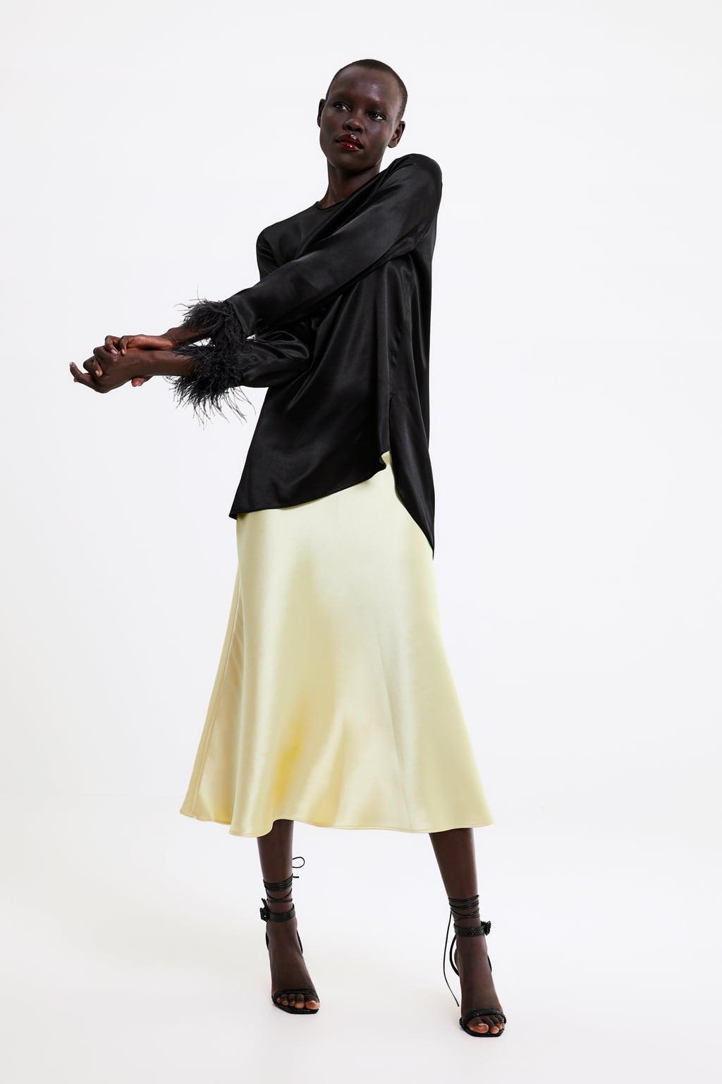 Модель в белой юбке миди и черной блузке