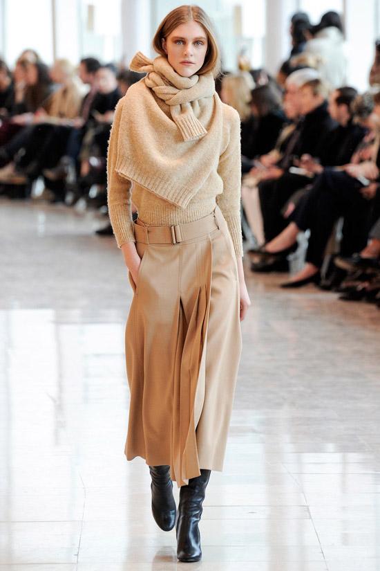 Модель в бежевой юбке миди и светлом свитере