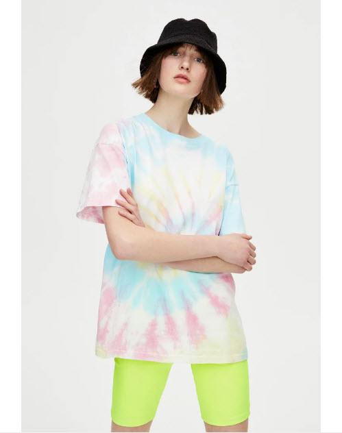 Модель в футболке оверсайз и зеленых вело шортах
