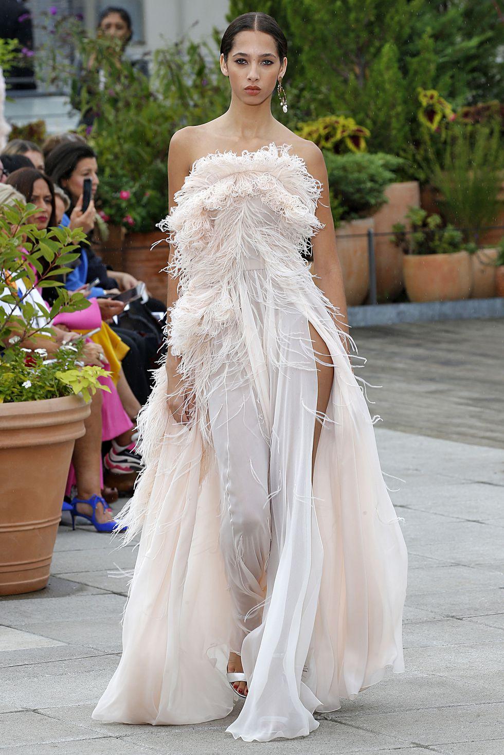 Модель в красивом белом платье с перьями