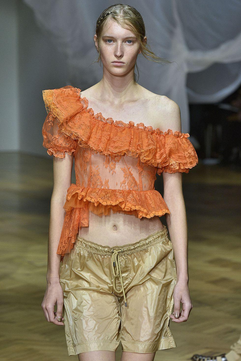 Модель в оранжевом кружевном топе на одно плечо и шортах
