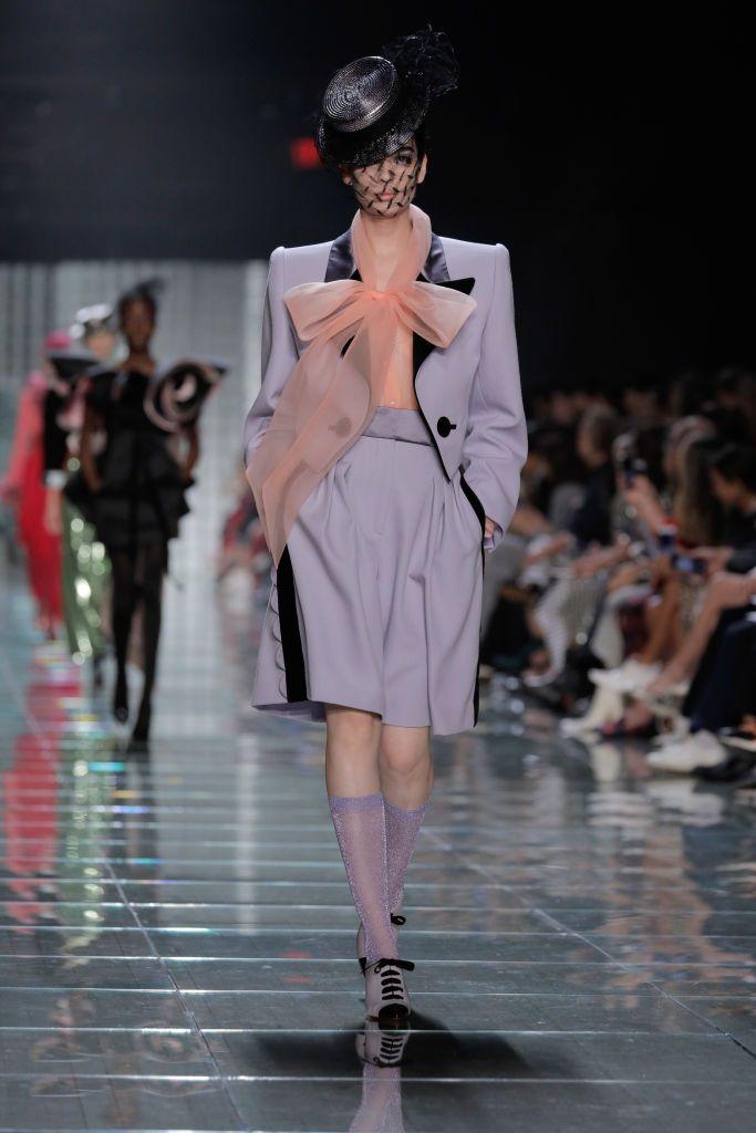 Модель в сером костюме с жакетом и легкой блузке