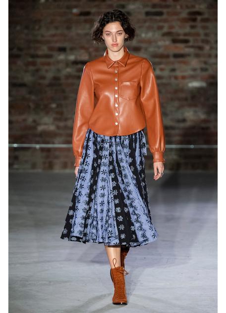 Модель в синей юбке миди и коричневой кожаной рубашке