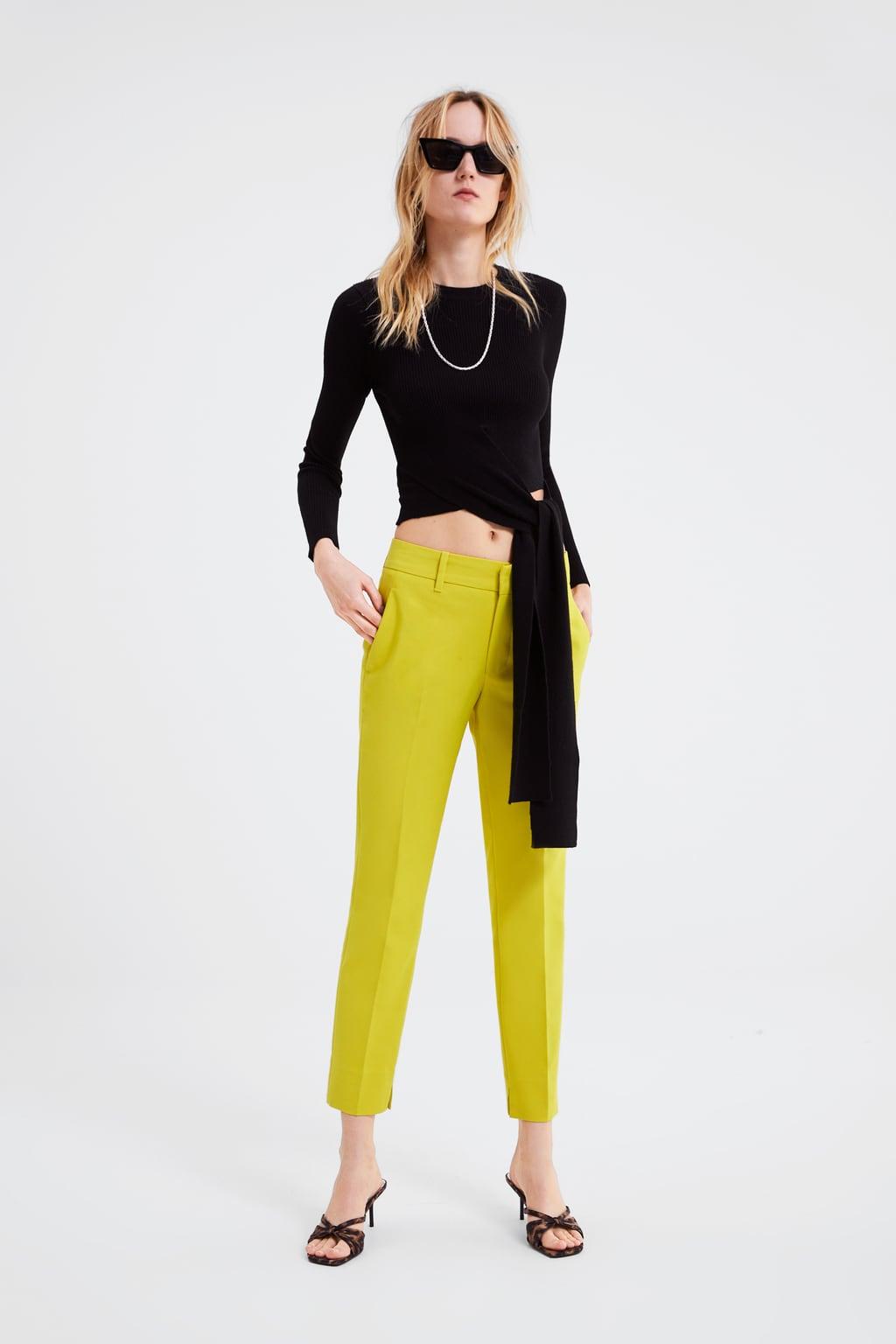 Модель в зеленых брюках и черном топе