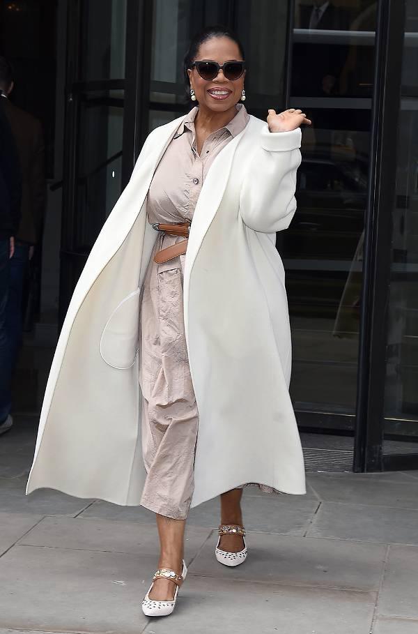 Опра Уинфри в бежвом платье с поясом и белом пальто