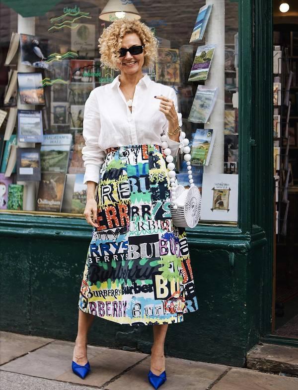 Renata Jazdzyk в белой блузке и пестрой юбке миди, синие туфли