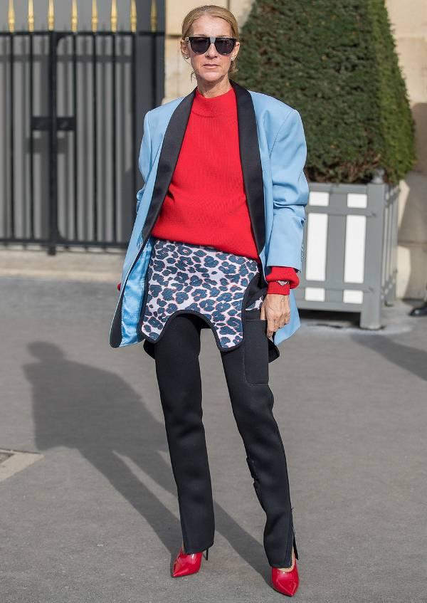 Селин Дион в черных брюках, касный свитер и голубой блейзер