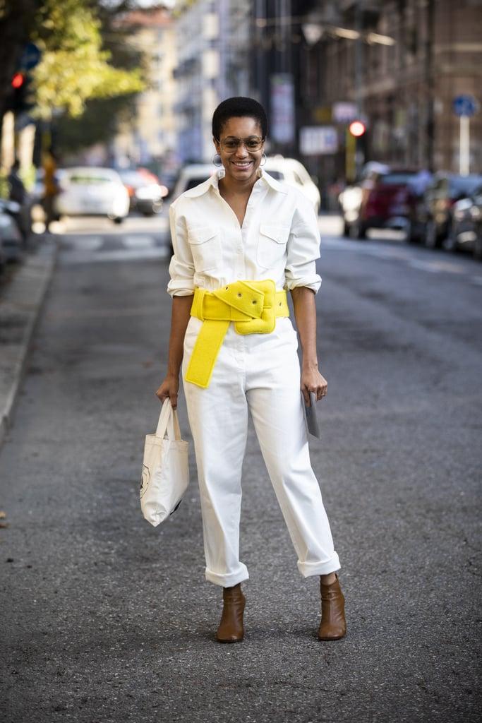 Девушка в белом комбинезоне с большим желтым ремнем и коричневые ботильоны