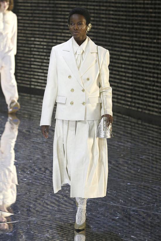 Девушка в белой юбке, жакет и серебристая сумочка