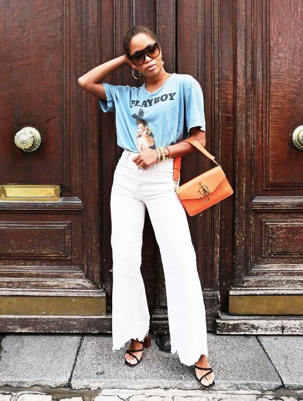 Девушка в белых джинсах клеш, голубая футболка и сумочка