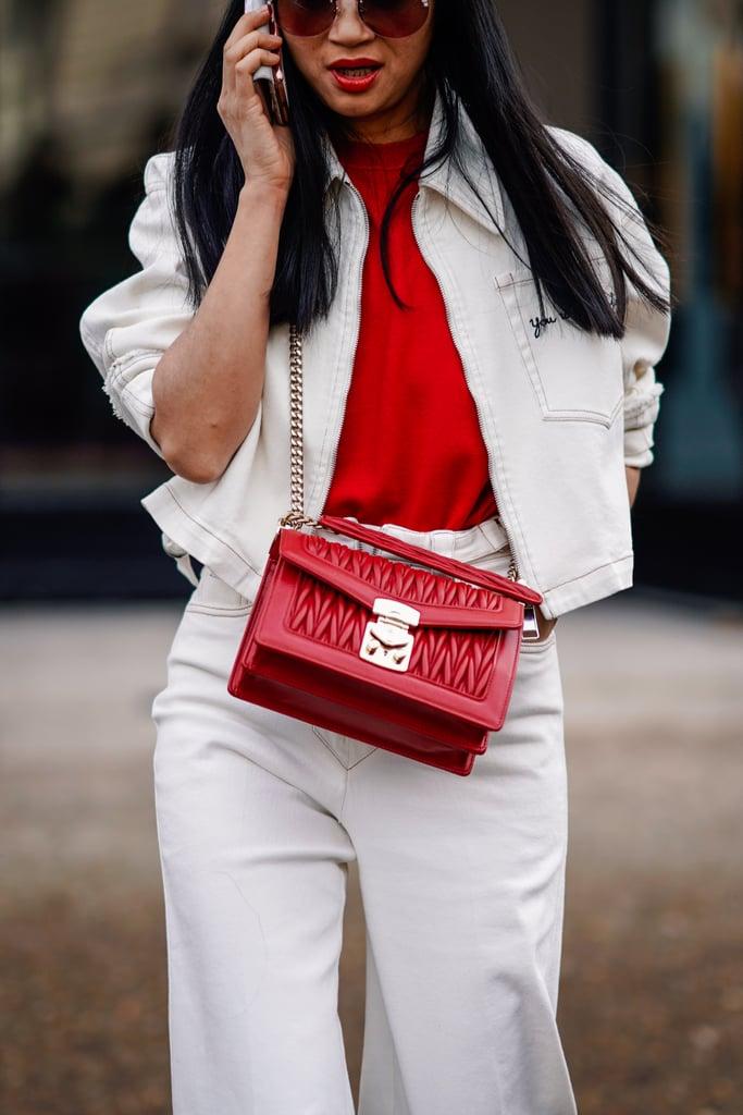 Девушка в белых широких джинсах, куртка и красная футболка и сумка