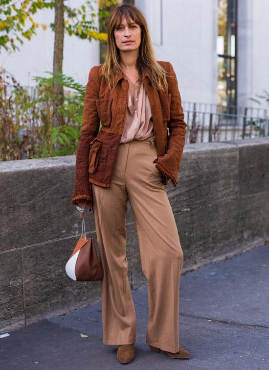 Девушка в бежевых брюках, блузка и коричнева куртка