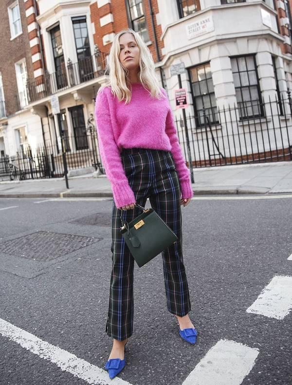 Девушка в брюках в клетку, розовый свитер и синие туфли