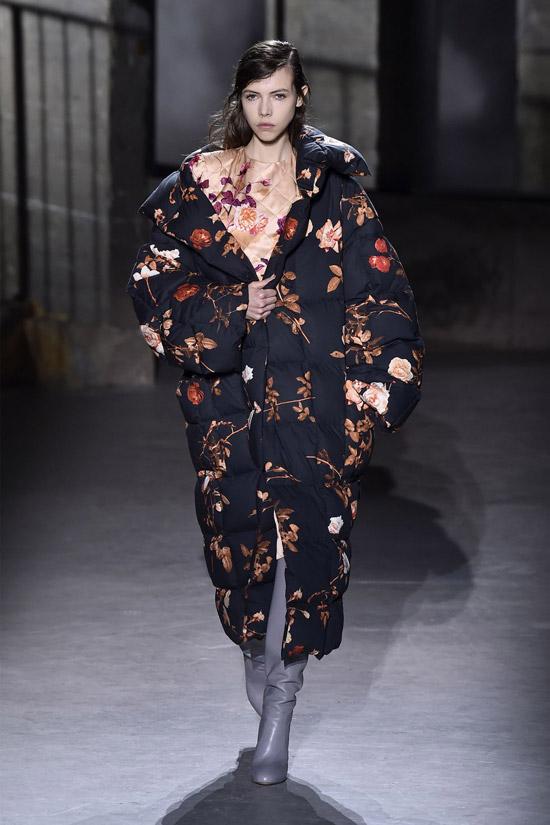 Девушка в черном пуховике с цветочным принтом, серые сапоги