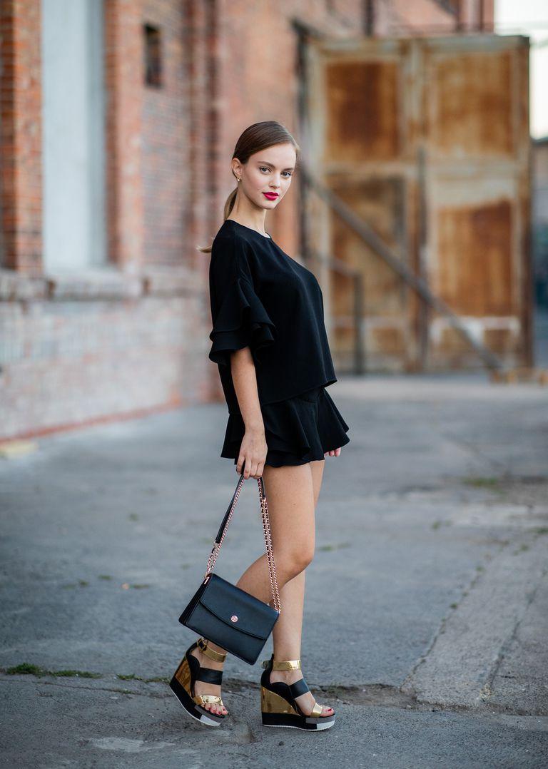 Девушка в черной мини юбке, кблузке и черных босоножках на танкетке