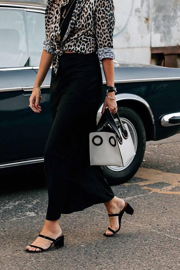 Девушка в черной юбке макси, рубашка с леопардовым принтом и черные сандалии
