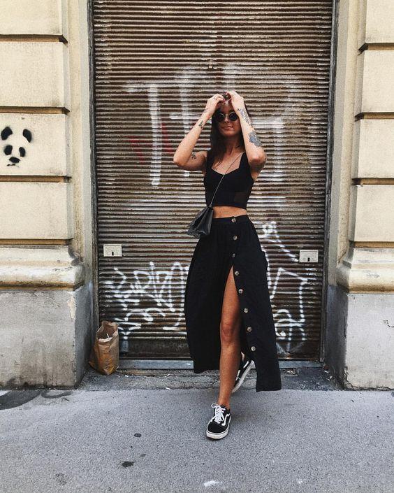 Девушка в черной юбке с пуговицами, кроп топ и черные кеды
