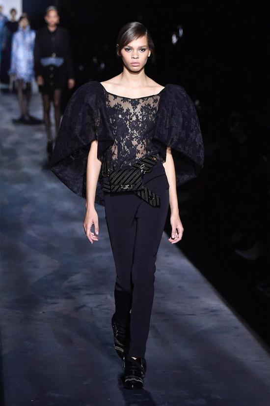 Девушка в черных брюках, блузка в объемными плечами и поясная сумка