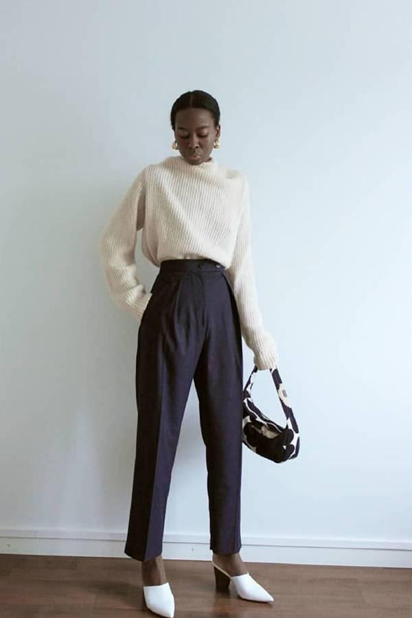 Девушка в черных брюках с высокой талией, белый джемпер и белые сабо