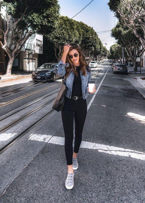 Девушка в черных джинсах скинни, джинсовка и кеды