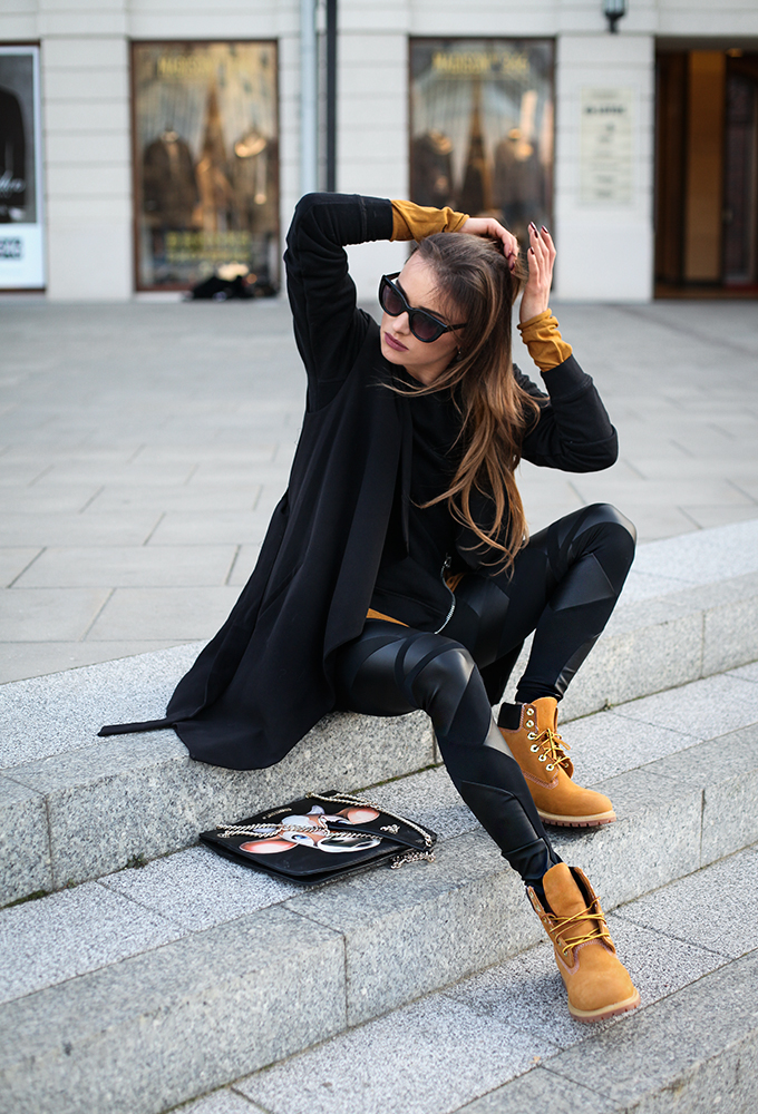 Девушка в черных леггинсах, кардиган и коричневые ботинки