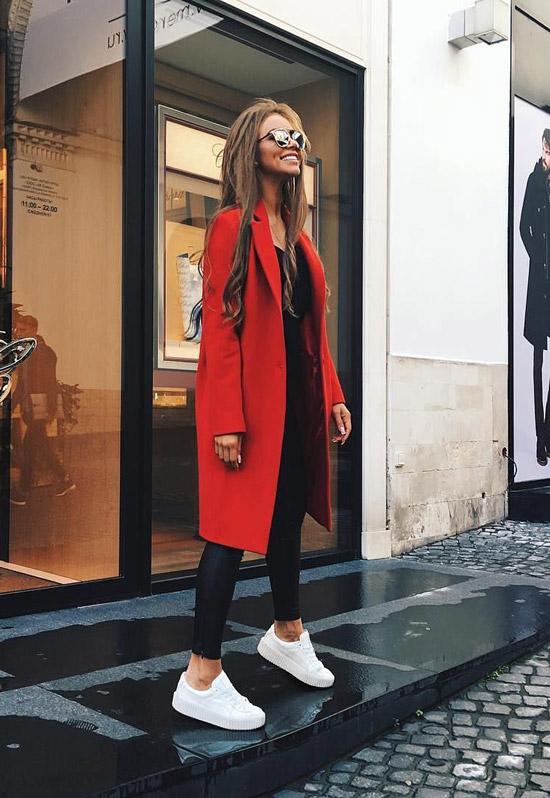 Девушка в черных леггинсах, красное пальто и белые кеды
