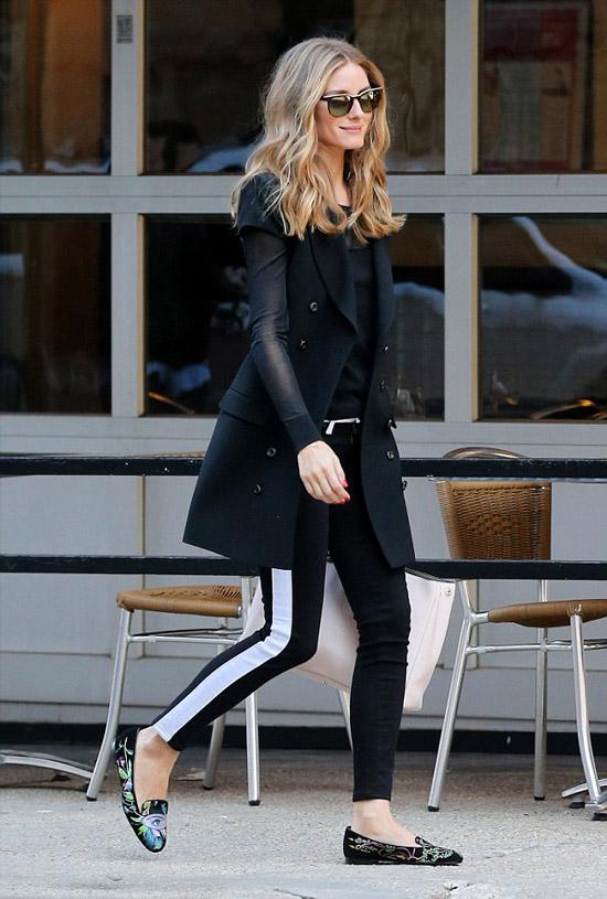 Девушка в черных леггинсах с белыми полосками, черное пальто и лоферы